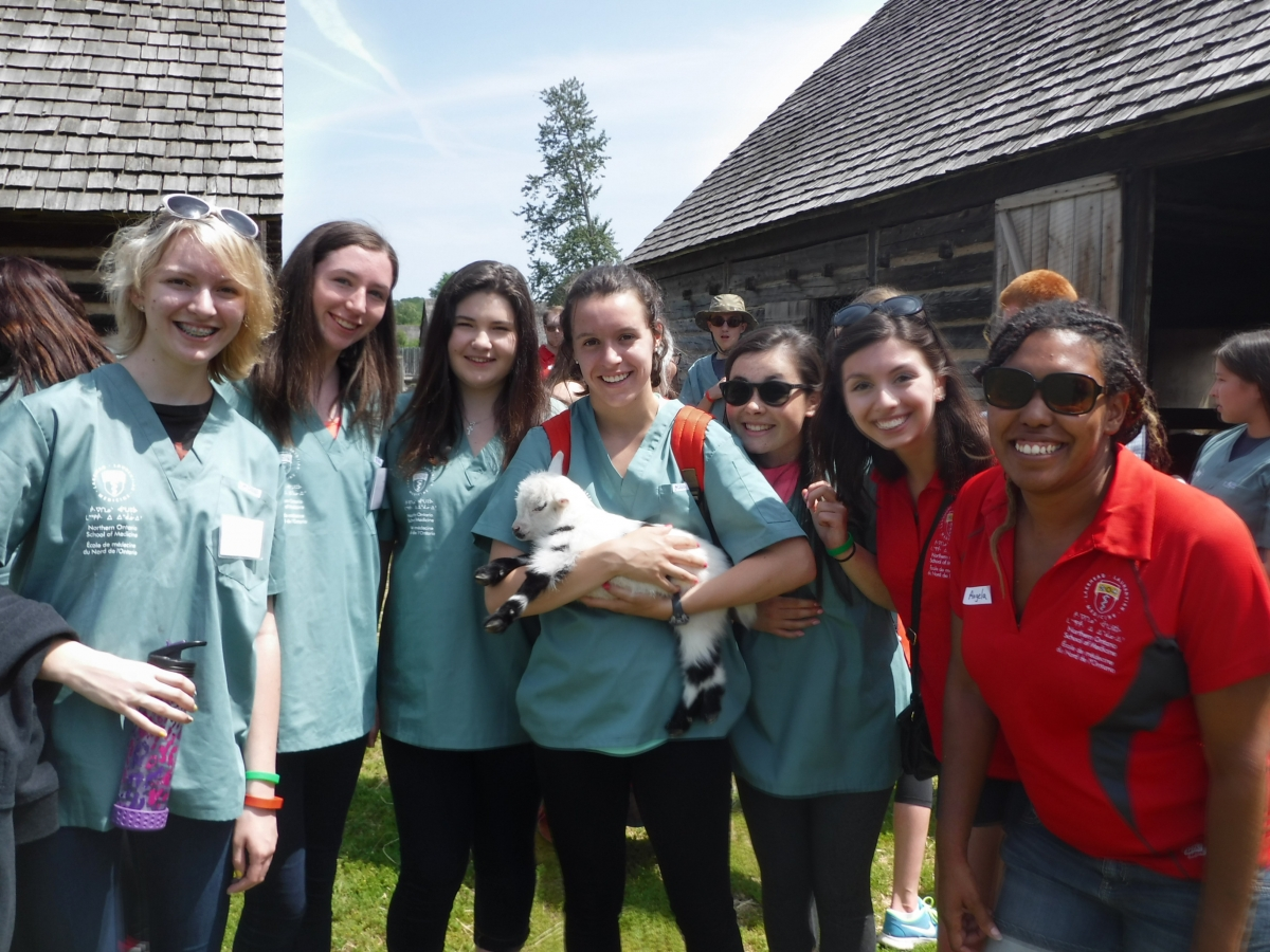 Campers and team leads pose for a photo with a baby goat at Fort William Historical Park