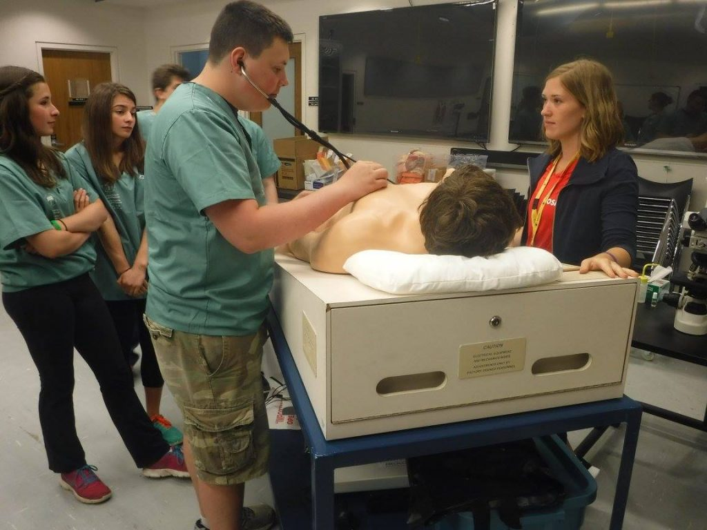 Camper practicing using a stethescope with SimMan 3G mannequin while team lead and fellow campers observe