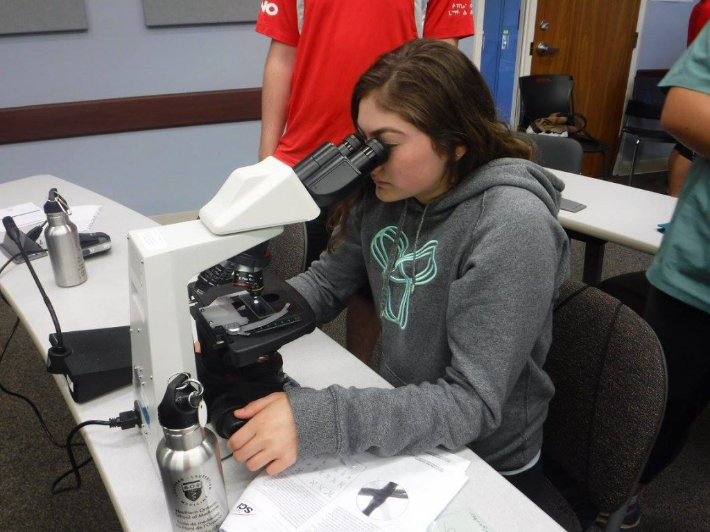 Camper looking at slide using a microscope