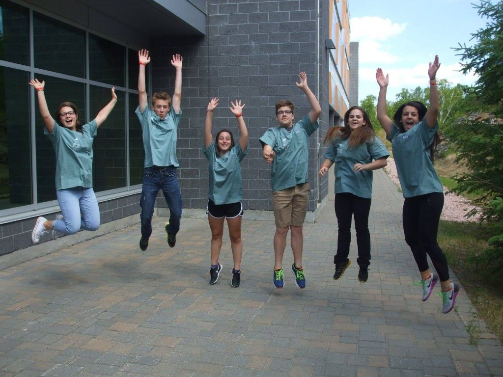 Campers jump into air for photo outside of medical school building