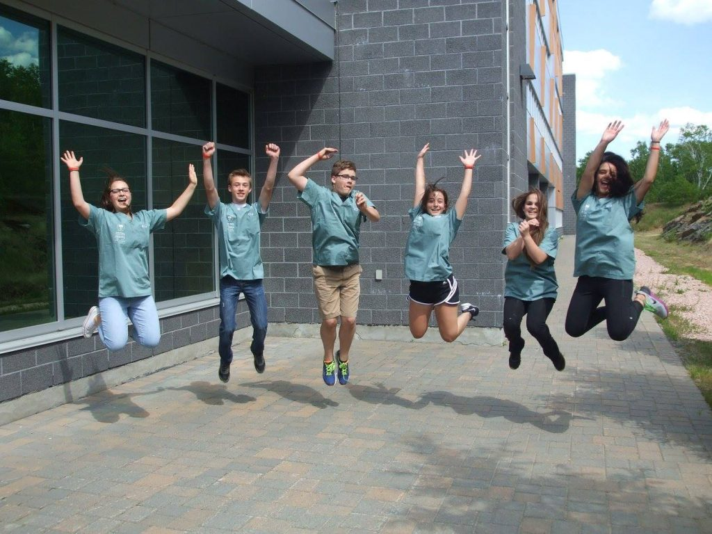 Campers pose for photo by jumping into the air outside of medical school building
