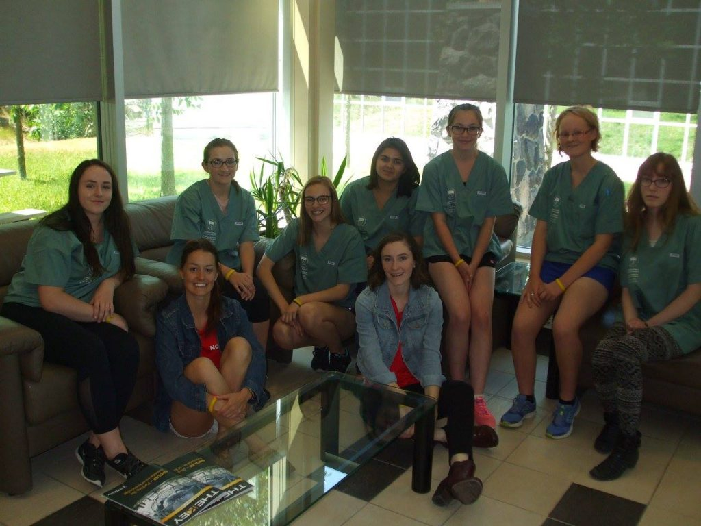 Camper team and two team leads pose for picture inside lobby of medical school while sitting on couches
