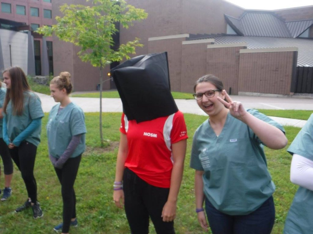 Camper gives peace sign beside team lead with bag on their head for ice-breaking activity