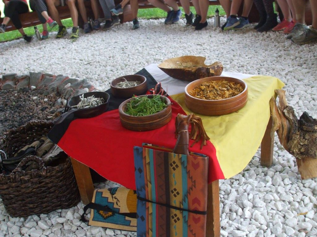 Photo of the four traditional Indigenous sacred fire items placed on a medicine wheel table cloth
