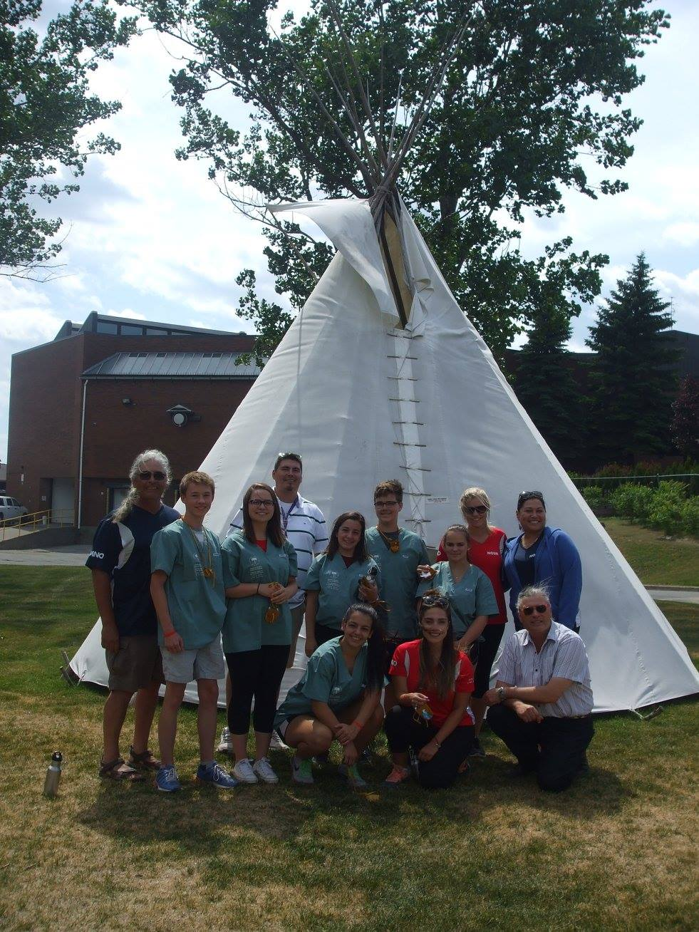 Camper team poses with NOSM staff members in front of teepee at Cambrian College