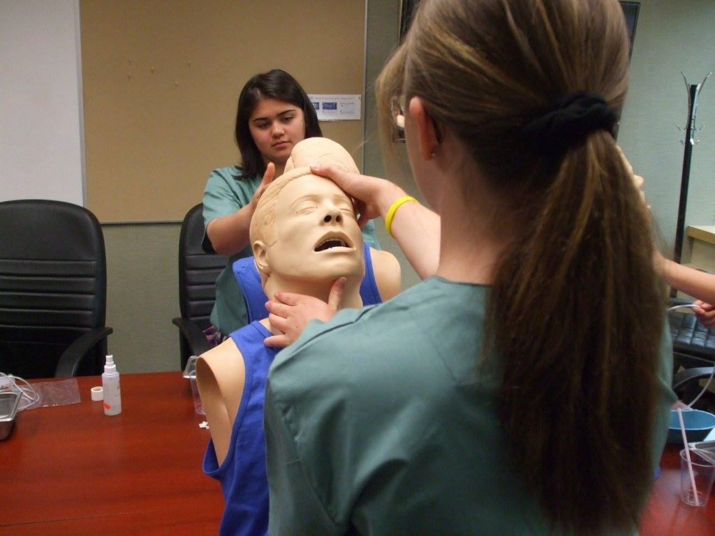 Campers prepare SimMan mannequin busts for inserting naso-gastric tubes