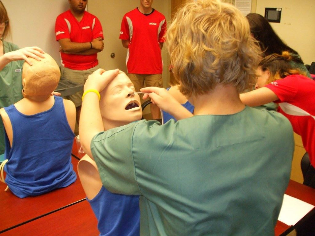 Campers practice inserting naso-gastric tubes into SimMan mannequin busts while three team leads supervise