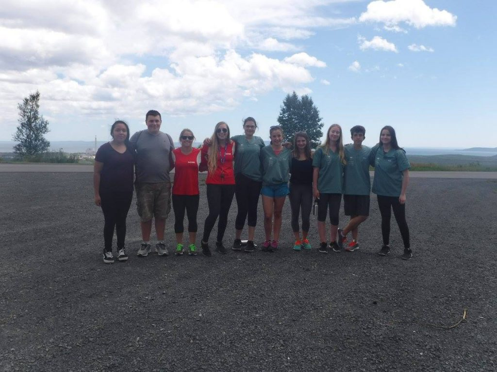 Team Leads pose with their camper team in parking lot of Mount McKay