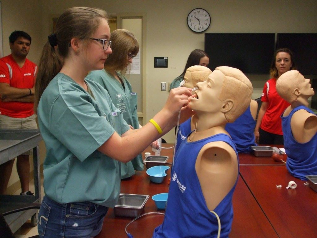 Campers practice inserting naso-gastric tubes into SimMan mannequin busts