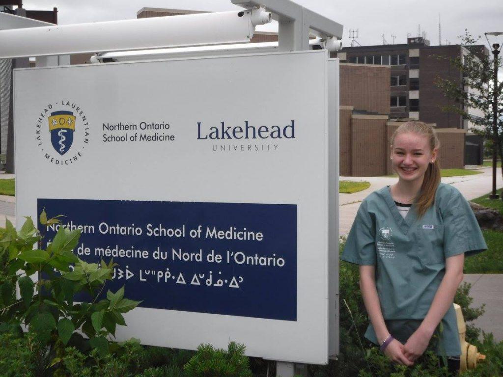 Camper poses beside Northern Ontario School of Medicine sign