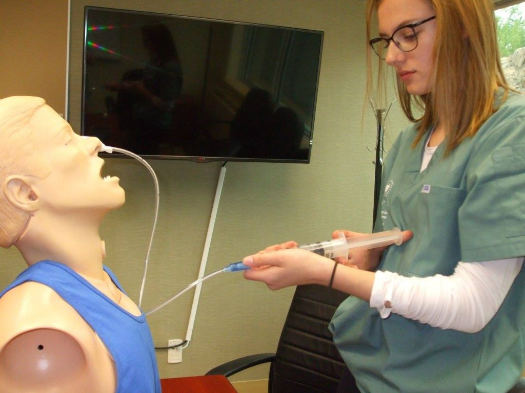 Camper practices asperates liquid from SimMan mannequin bust through naso-gastric tube
