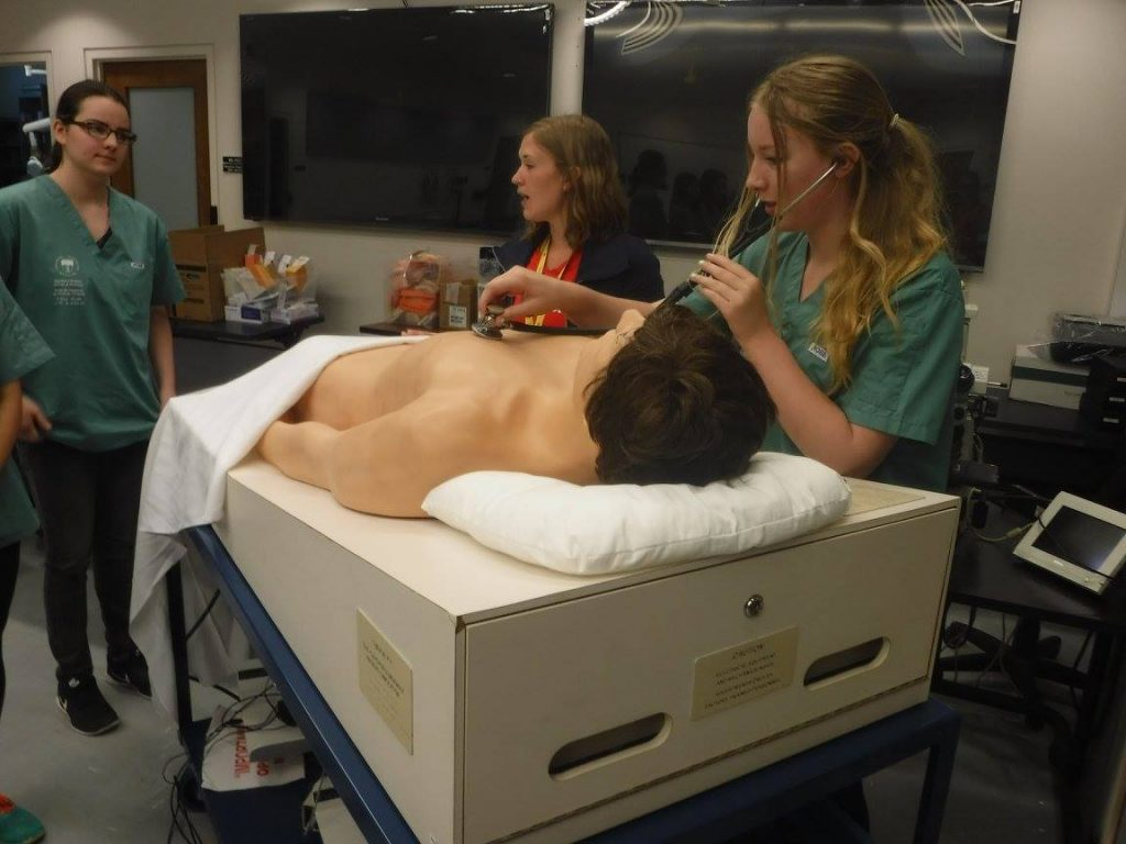 Camper practicing using a stethescope with SimMan 3G mannequin