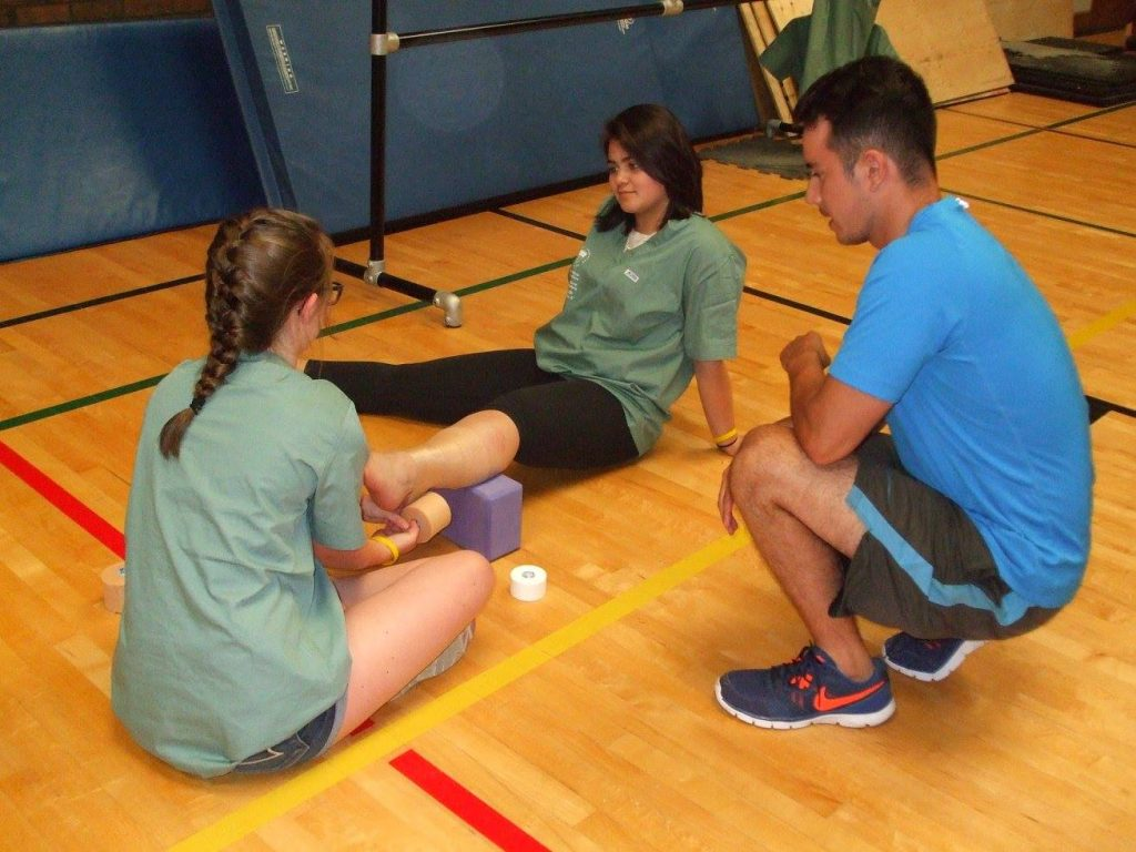 Camper practices wrapping ankle of fellow camper while instructor supervises