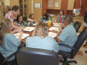 Retired surgeon teaches proper suturing technique to group of campers sitting around a table in lab