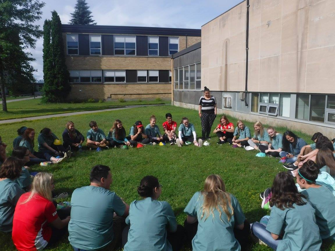 Campers sitting outside in a circle participating in a mask sharing exercise