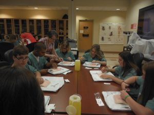 Retired surgeon teaches proper suturing technique to group of campers sitting around table in lab