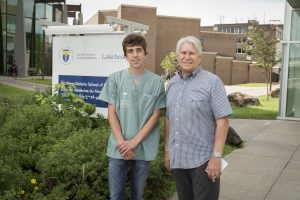 Photo of a camper standing with a sponsor outside of medical school building in front of Northern Ontario School of Medicine sign
