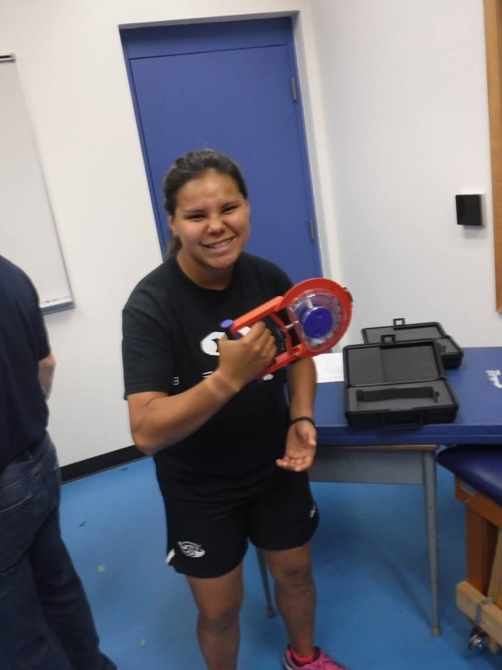 Camper grimaces while using grip-strength testing instrument