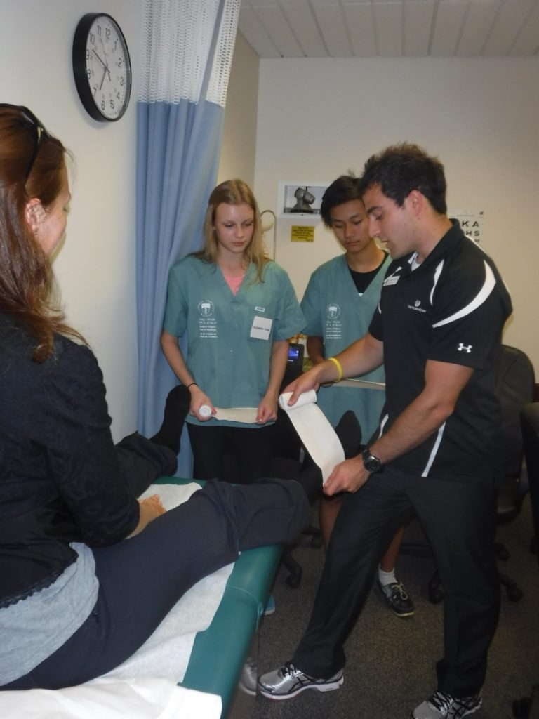 Physiotherapist demonstrating how to tape an ankle on assistant while two campers observe