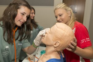Team Lead supervises camper practicing inserting a naso-gastric tube into simulation mannequin bust