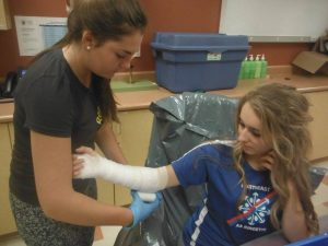 Camper wraps casting gauze around fellow camper's arm