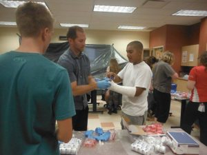 Physician Assistant assists camper with casting fellow campers arm