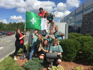 Campers and team leads pose for picture with Franco-Ontarian flag in front of Northern Ontario School of Medicine sign