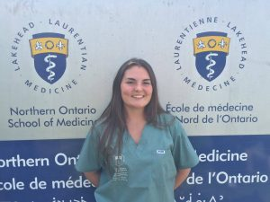 Camper poses for picture in front of Northern Ontario School of Medicine sign