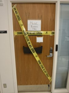 Door to Music Room covered with yellow crime scene do not cross tape