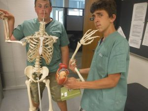 Two campers strike a funny pose with skeleton model