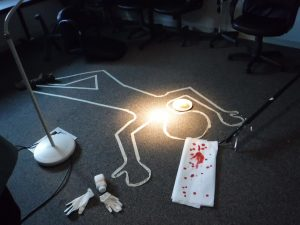 Staged crime scene with chalk outline of body, towel with blood droplets, gloves, a bottle and a plate on the floor