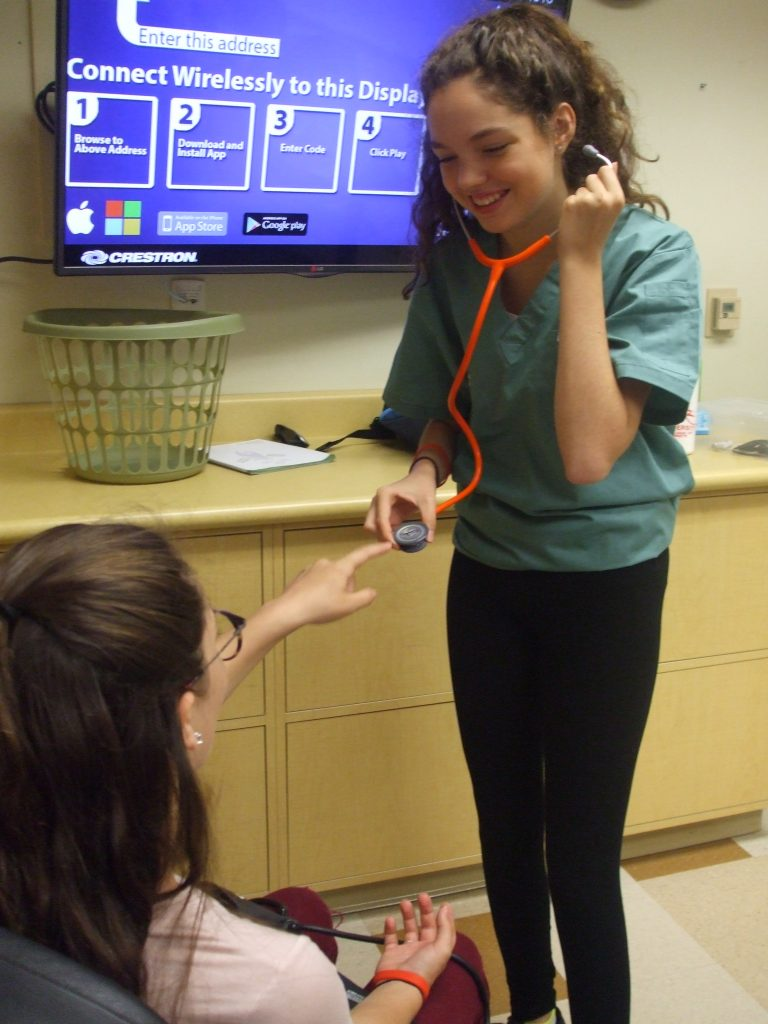 Camper places finger on stethescope diaphragm while fellow camper places ear tips in ears