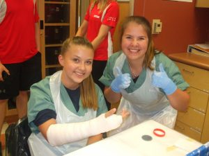 Camper gives double thumbs up after completing cast on fellow campers arm. Camper with casted arm displays their arm