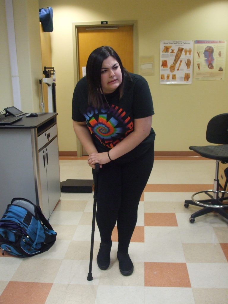 Camper leans heavily on cane during physiotherapy activity with a pained facial expression