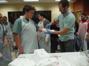 Physician assistant begins to remove cast from campers arm