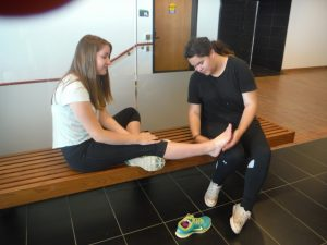 Camper inspects fellow campers ankle during wrapping activity