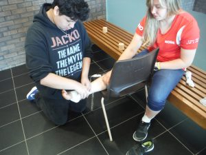 Team lead sits and props ankle up on chair while camper adjusts ankle wrapping material