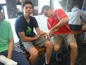 Team lead adjusts tape on campers wrist