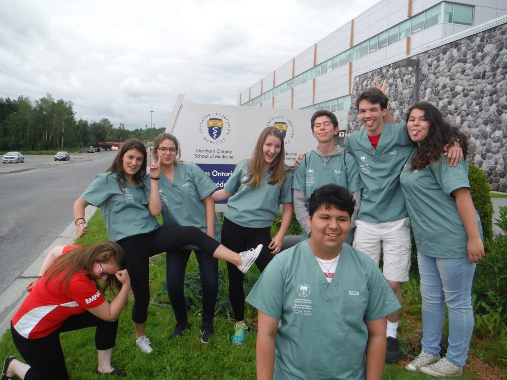Campers and team lead strike funny pose for group photo in front of Northern Ontario School of Medicine sign