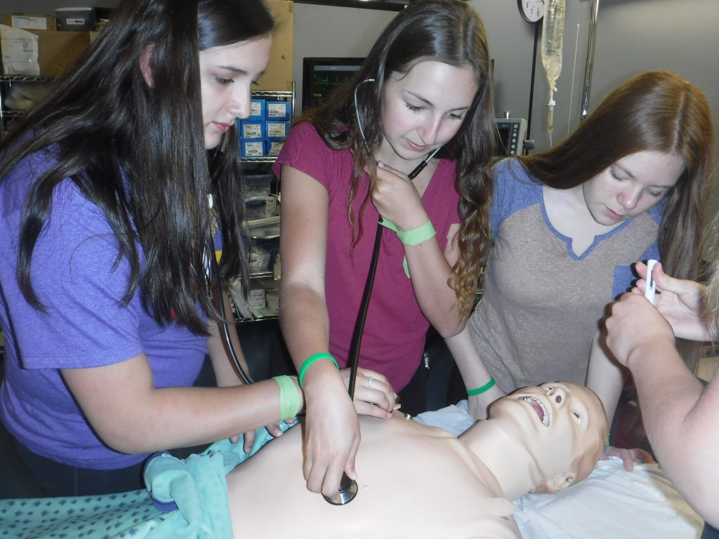 Three campers pratice checking vitals on SimMan 3G mannequin using stethescopes