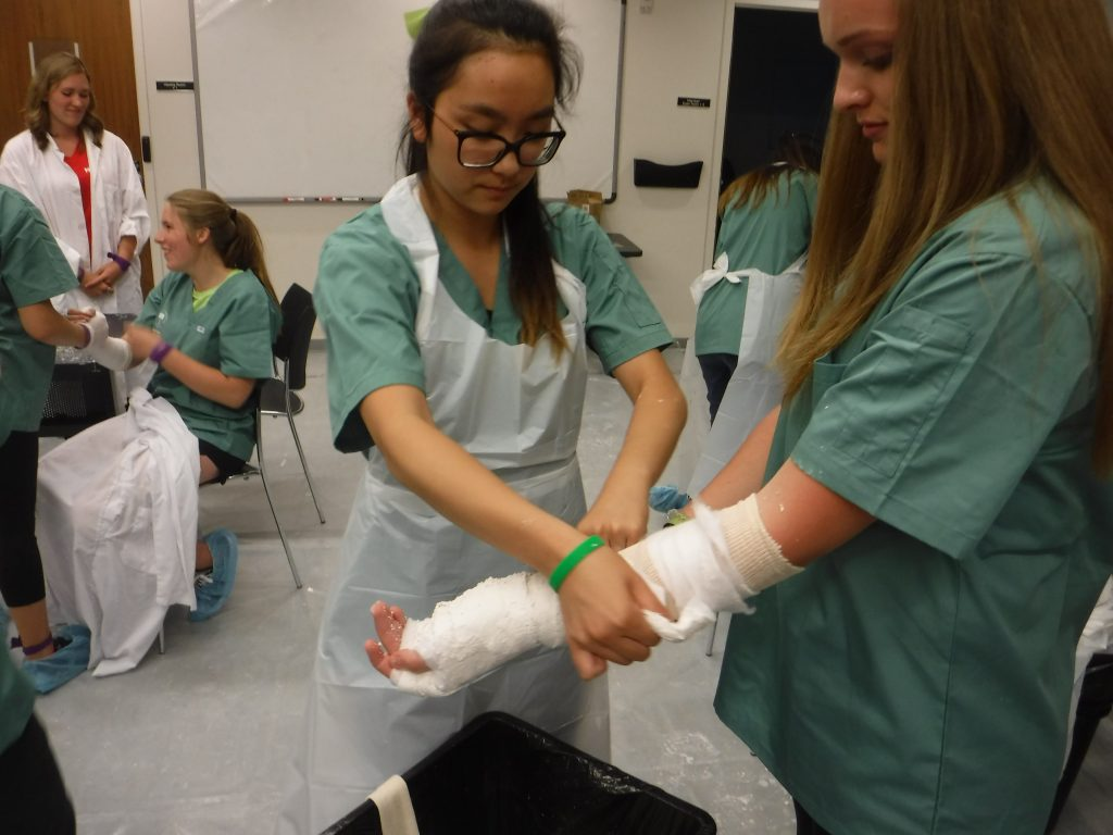 Camper applies casting material to fellow camper's arm in lab while in background fellow campers and team lead also participate in casting activity