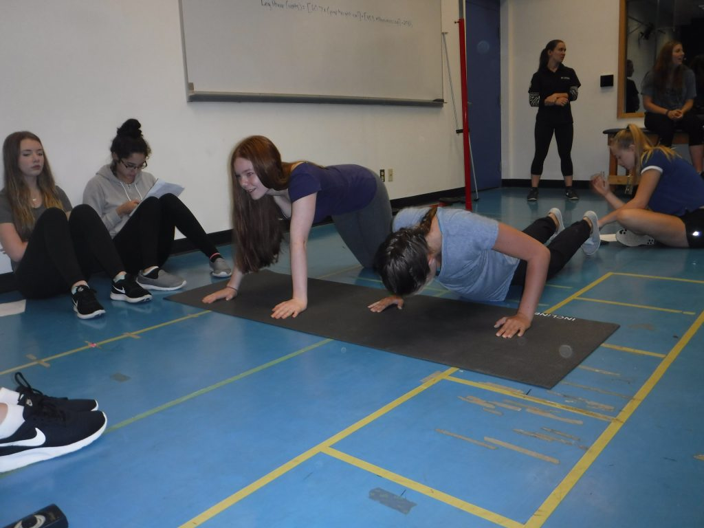 Two campers perform push ups in Kinesiology classroom while fellow campers look on