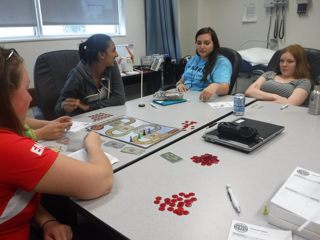 Campers and team lead play Social Determinants of Health boardgame in small group room