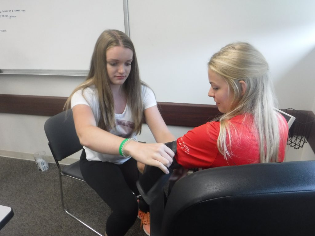 Camper puts sphygmomanometer (blood pressure cuff) on team lead in small group room