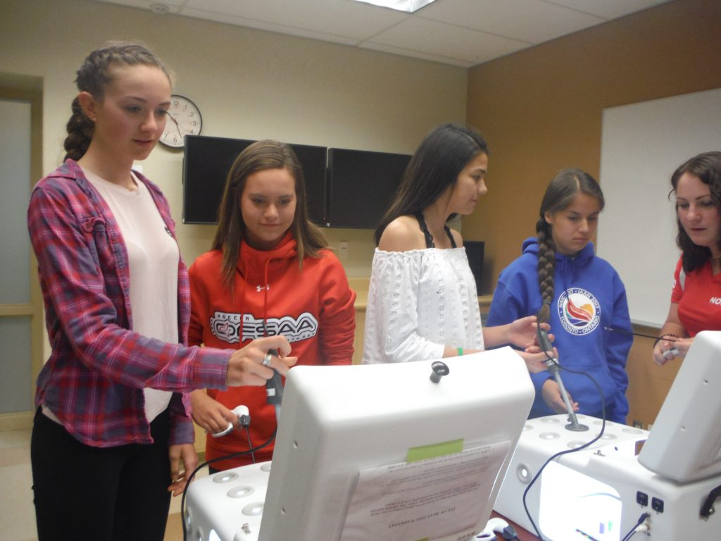 Campers use laproscopic simulator in tandem while beside them team lead instructs two other campers on a laproscopic simulator