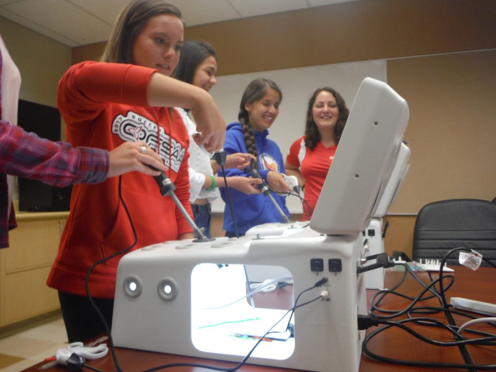 Side angle photo of campers using laproscopic simulator in tandem while beside them team lead instructs two other campers on laproscopic simulator