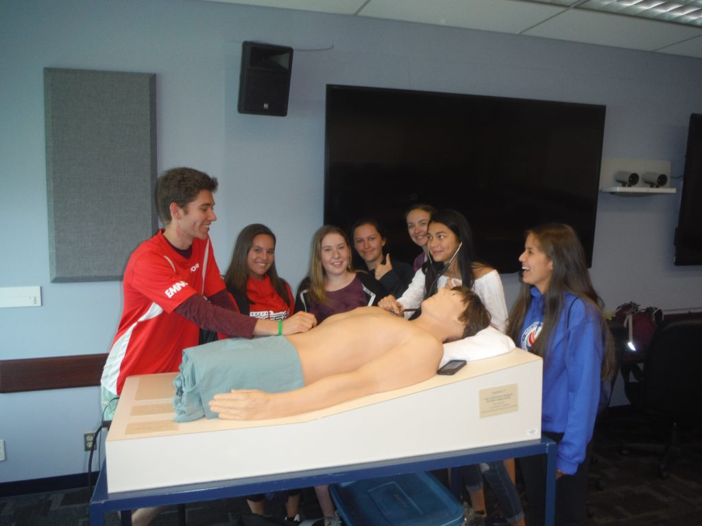 Team lead supervises camper using stethescope on SimMan 3G mannequin while fellow campers look on