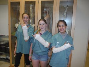 Three campers display their casted arms in lab