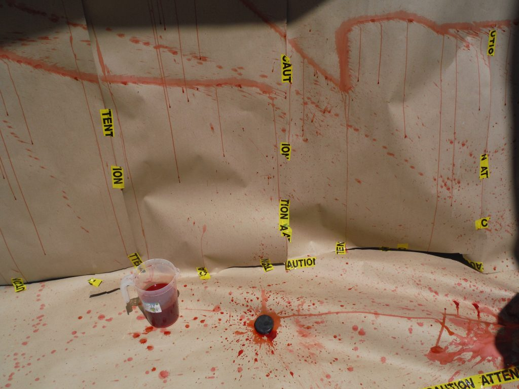 Picture of blood spatter analysis set up: fake blood spattered on butcher paper covering wall with a pitcher of fake blood and a hockey puck laying on the ground