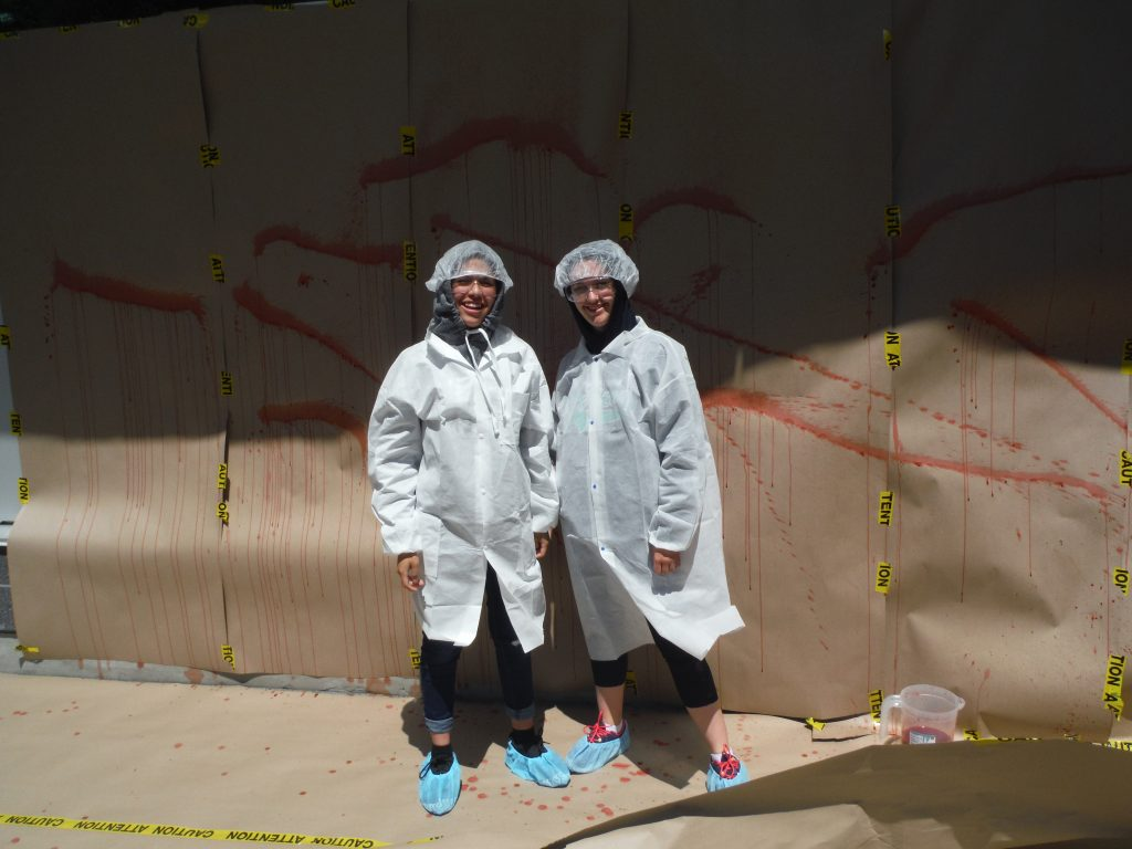 Two campers pose for photo in their CSI coats, caps, and booties in front of blood spatter analysis wall